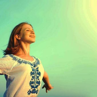 happy young woman open her arms to the sky and enjoying life